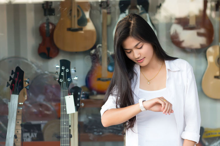 Young Woman Checking Time While Standing Against Guitar Store