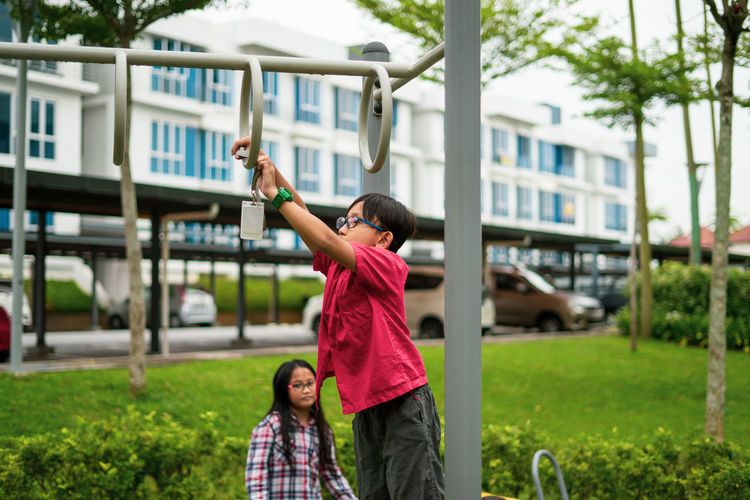 Young asian children hang on the monkey bar. to exercise at outdoor playground in the neighbourhood.