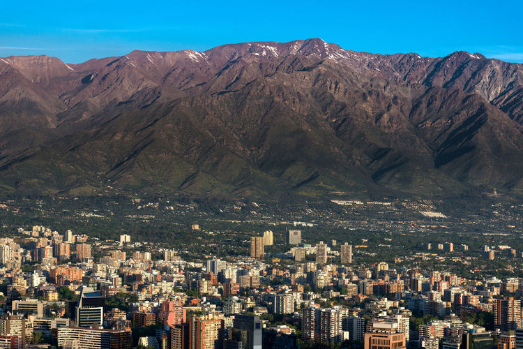 The andes mountain range with buildings of the wealthy district of providencia in santiago de chile.