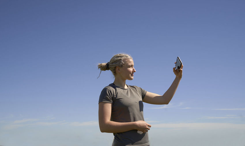 Full length of woman standing on mobile phone against blue sky