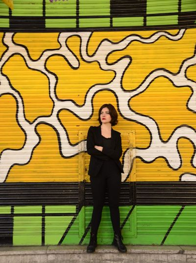 Thoughtful young woman standing against yellow shutter