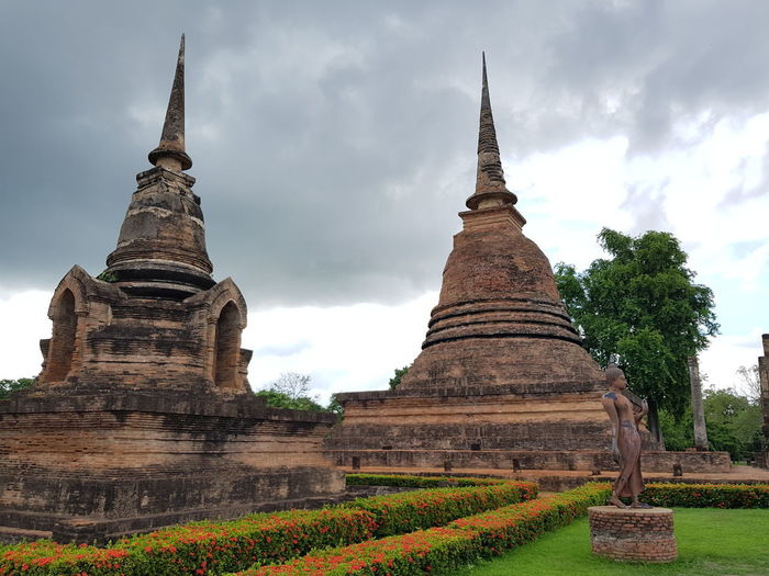 View of old temple building against cloudy sky