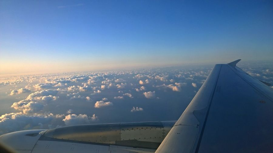 Cropped Image Of Airplane Flying Above Clouds In Sky