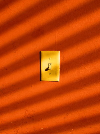 Close-up of switch on orange wall