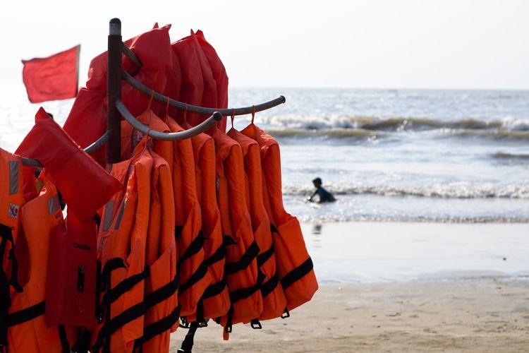Red umbrella on beach against clear sky