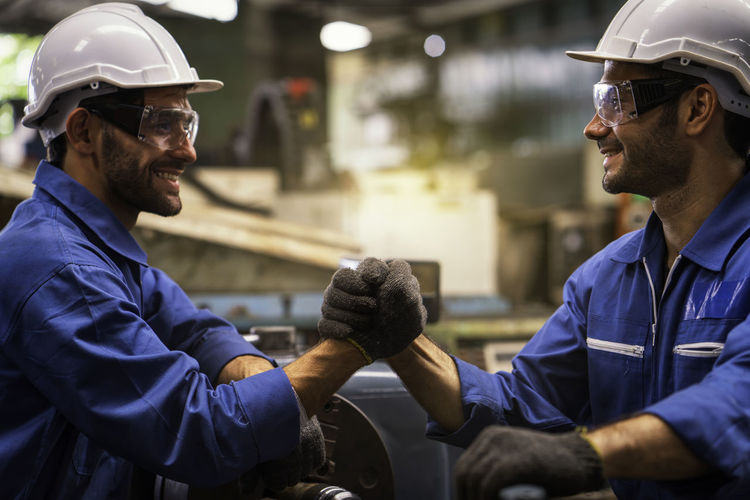 Smiling workers shaking hands while working at factory