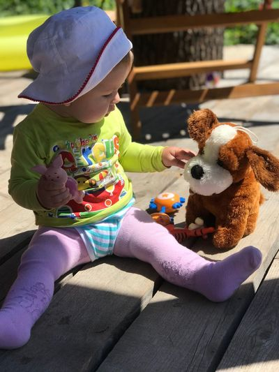 Midsection of woman with toy sitting outdoors