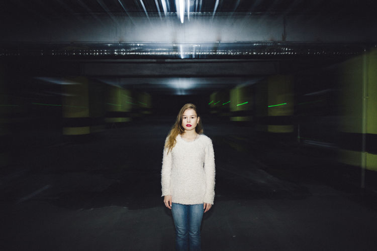 Portrait of beautiful woman standing at underground parking lot