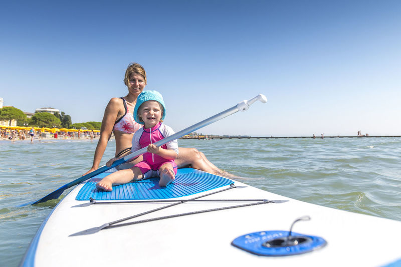 Happy Mother And Girl On Paddleboard
