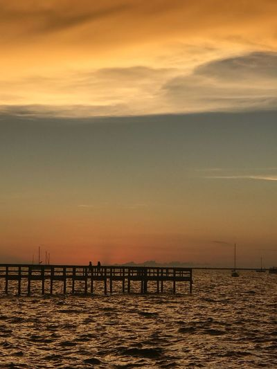 Silhouette pier on sea against sky during sunset