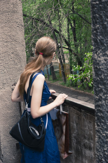 Young woman standing by railing in park