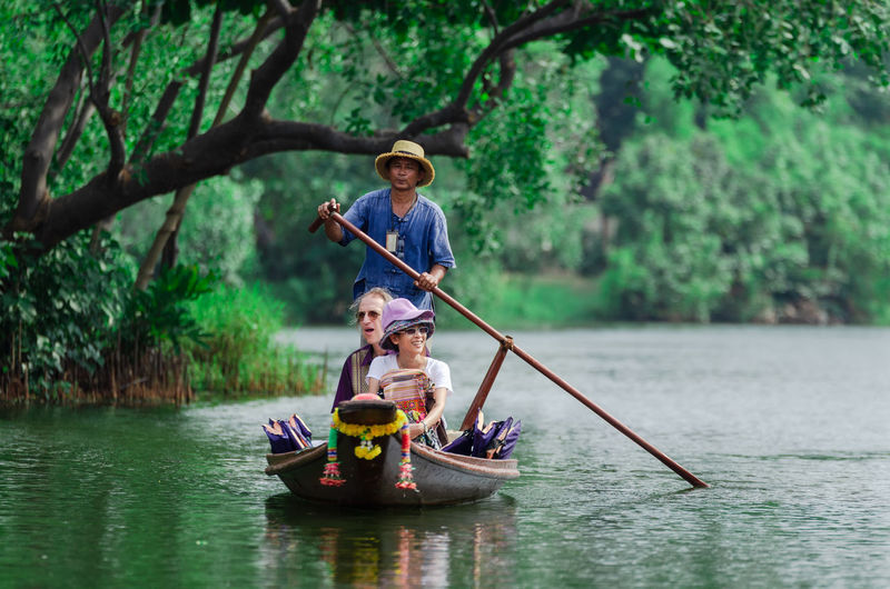 People rowing boat in river against trees