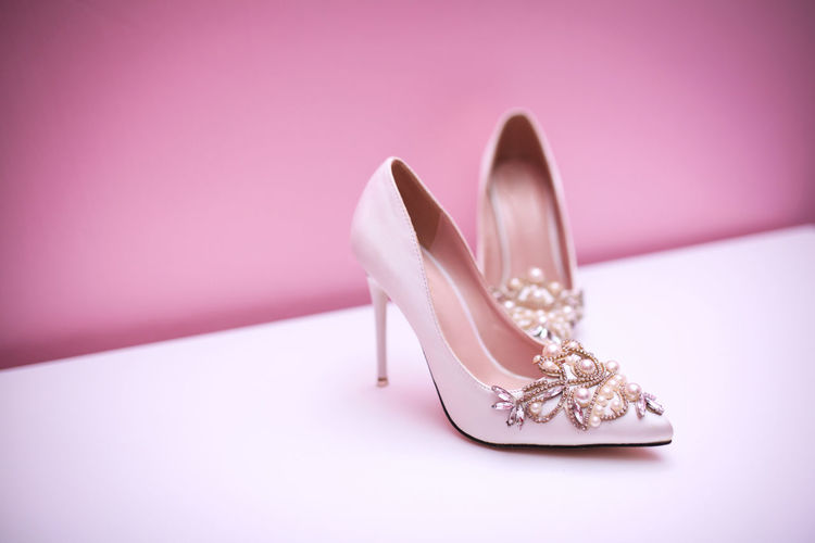 Shoes on table against pink background