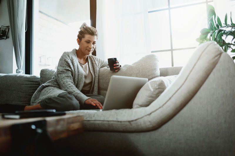 Low angle view of woman using laptop while sitting on sofa at home