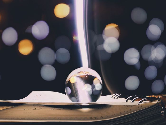 Close-up of crystal ball on book against light