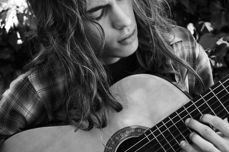 Close-up of teenage boy playing guitar