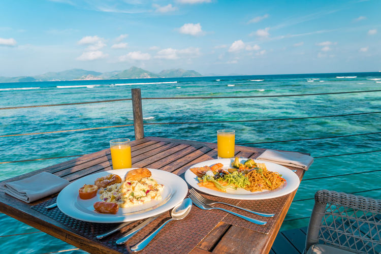 Food on table by swimming pool against sea, la digue seychelles