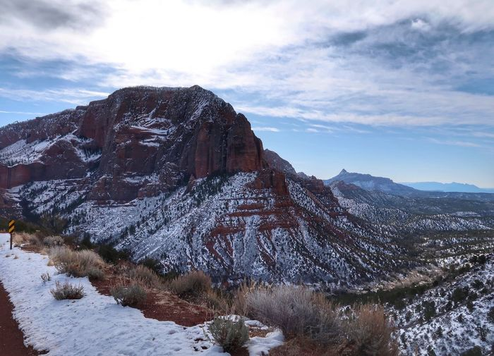 Landscape of red snow-dappled mountain and surrounding are in Zion National Park Premium Collection Zion National Park Snow Winter Tranquility Cold Temperature Beauty In Nature Mountain Tranquil Scene Travel Destinations Snowcapped Mountain Physical Geography No People Outdoors Day Mountain Range Cloud - Sky Landscape Weather Sky Nature Scenics