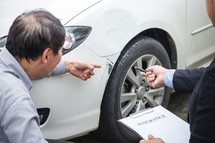 Man Showing Scratched Car To Insurance Agent With Form