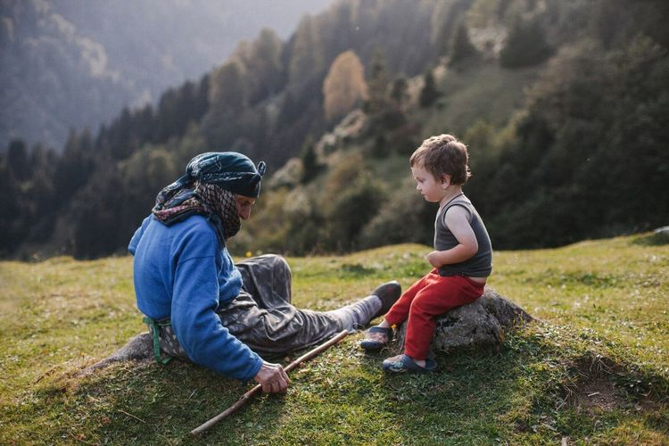 Father and son sitting on mountain
