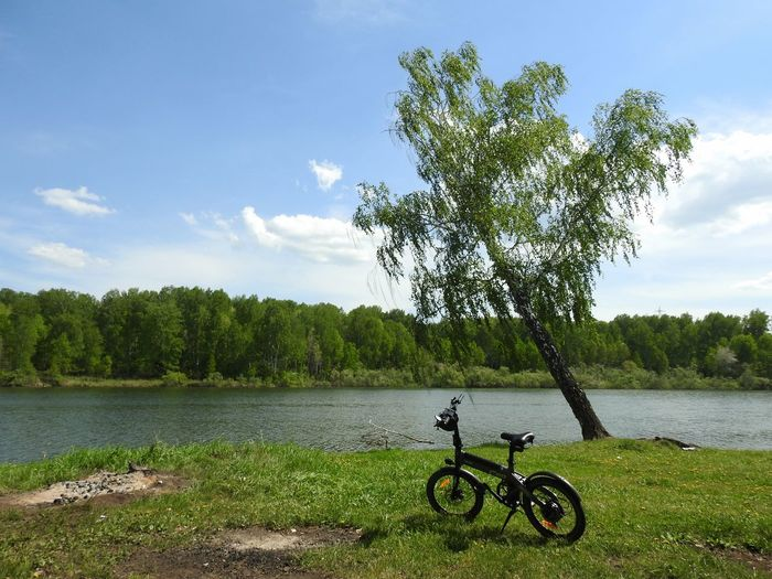 Bicycle by lake against sky