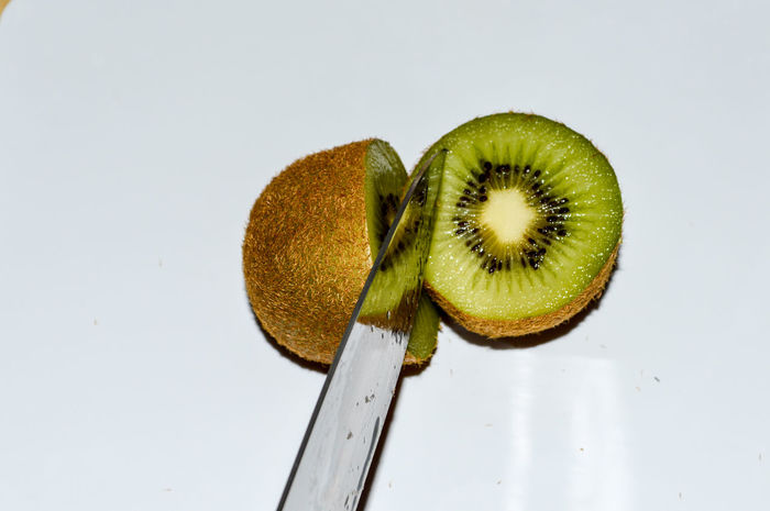 Cut your Kiwi Kiwi - Fruit Kiwi Fruit Food Food And Drink Healthy Eating Freshness Green Color SLICE Close-up Detail Still Life Halved Knife Cross Section White Background Vitamines Simplicity Minimal Minimalobsession Ready-to-eat TheWeekOnEyeEM