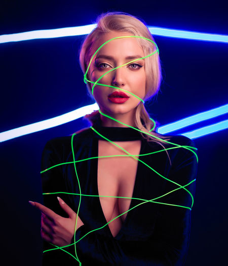 Fashion art photo of elegant blonde model in seductive wear with light neon colored club spotlights Adult Beautiful People Beautiful Woman Beauty Black Background Blue Fashion Front View Hair Hairstyle Illuminated Indoors  Laser Light Long Exposure Looking At Camera Neon Nightlife One Person Portrait Studio Shot Women Young Adult Young Women
