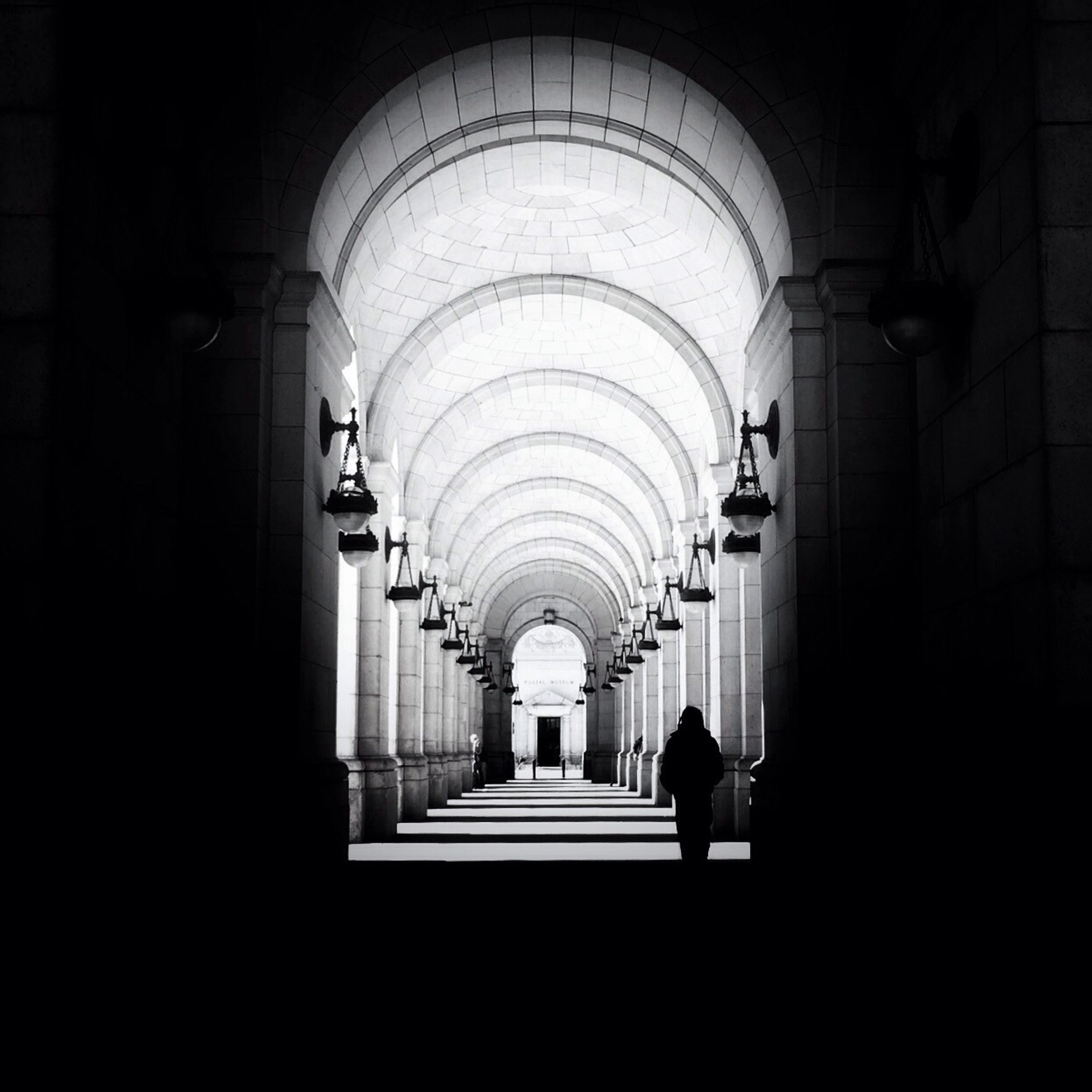 indoors, arch, architecture, corridor, ceiling, built structure, the way forward, diminishing perspective, men, walking, tunnel, rear view, full length, illuminated, architectural column, archway, lighting equipment, silhouette, in a row