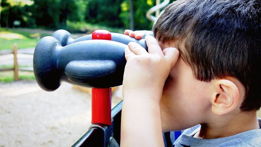 Close-Up Of Boy Looking Through Binoculars At Park