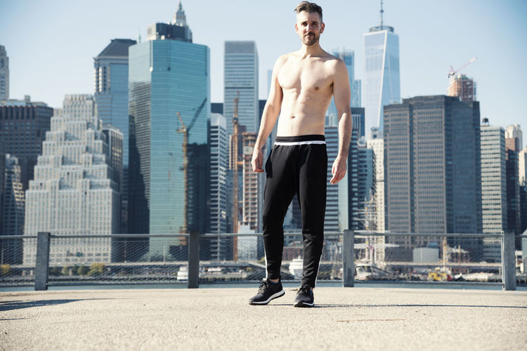 Full length of shirtless man standing on building terrace in city