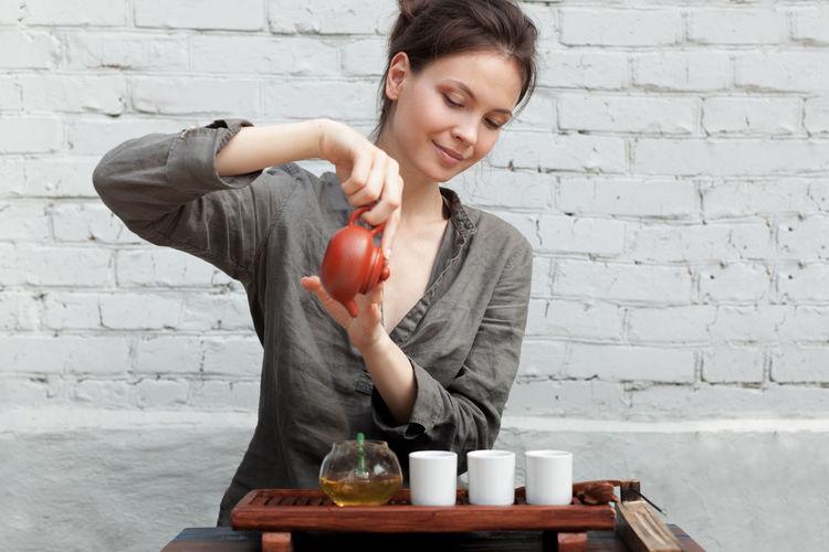 Woman pouring tea in mug against brick wall