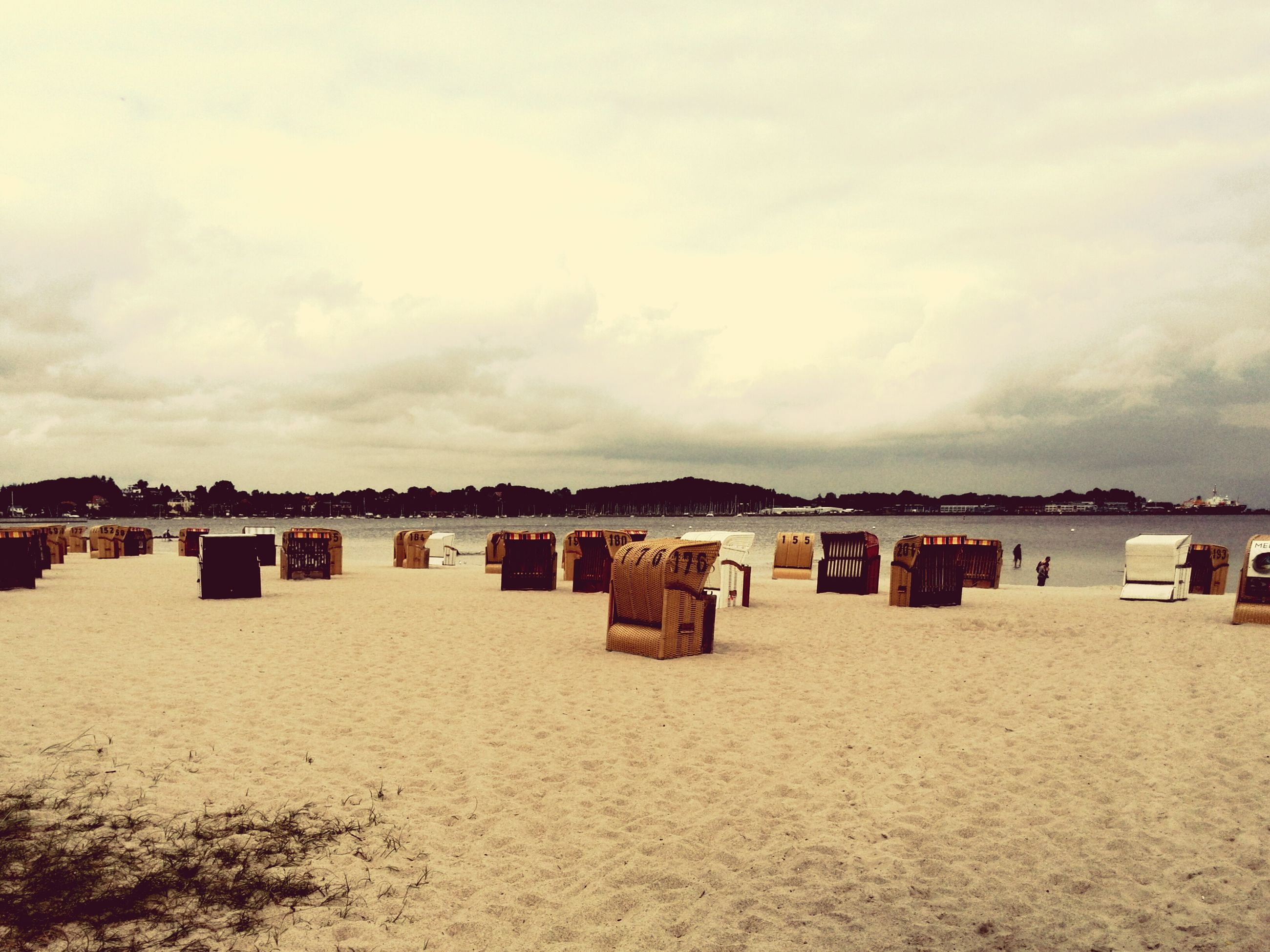 beach, sand, sea, sky, water, shore, in a row, tranquil scene, tranquility, scenics, cloud - sky, nature, beauty in nature, day, vacations, cloud, cloudy, outdoors, travel destinations, tourism, idyllic, side by side, coastline, no people, repetition, non-urban scene, remote, ocean, arrangement