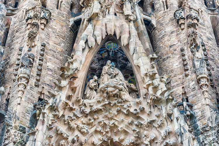 BARCELONA - AUGUST 9: Detail of the Nativity Facade of the Sagrada Familia, the most iconic landmark designed by Antoni Gaudi in Barcelona, Catalonia, Spain, as seen on August 9, 2017 Architecture Low Angle View Built Structure Art And Craft The Past Building Exterior Day Human Representation Craft Representation Place Of Worship History Travel Destinations Sculpture Creativity No People Building Statue Carving - Craft Product Male Likeness Outdoors Ornate Carving