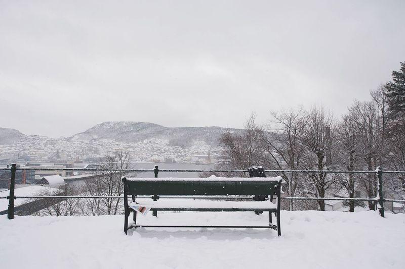 Empty Frozen Bench Against Sky