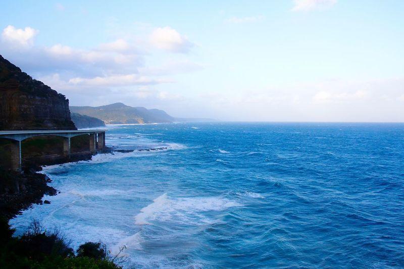 Elevated coastal road by sea against sky