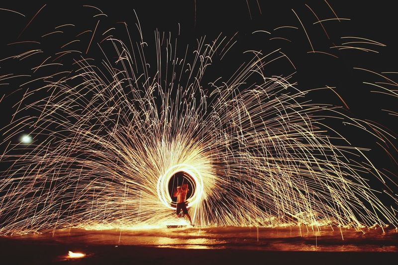 Man with wire wool on shore at night