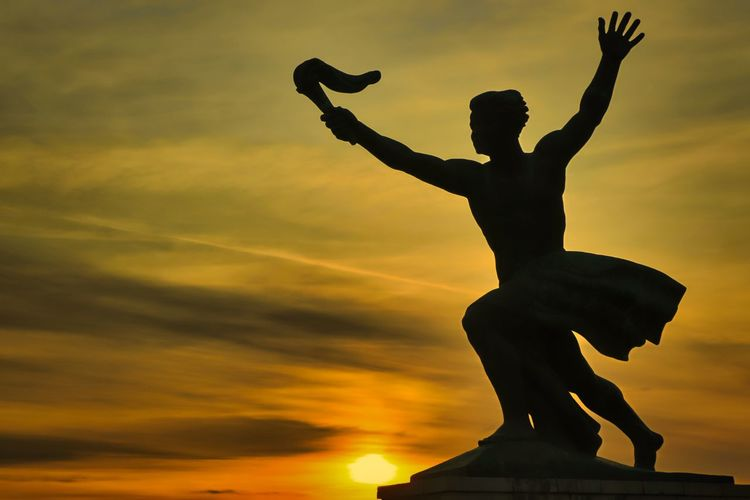 Low angle view of silhouette statue against sky during sunset