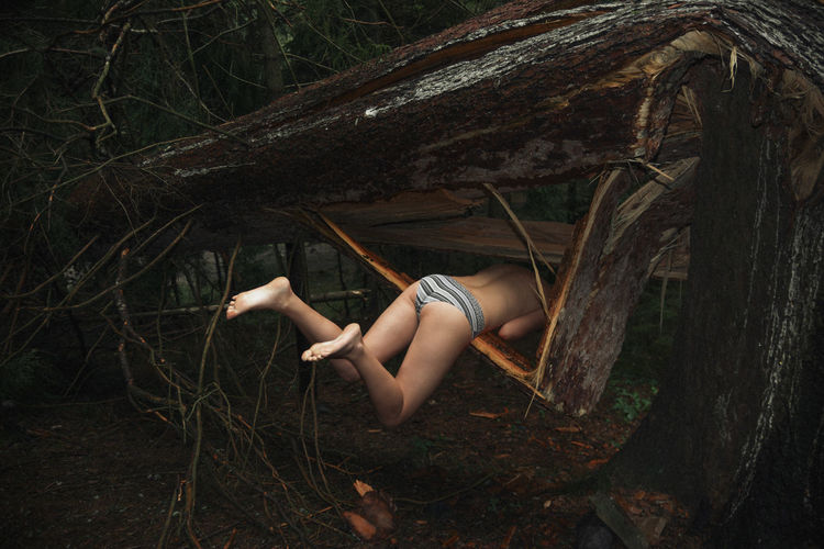 Woman relaxing on tree trunk in forest