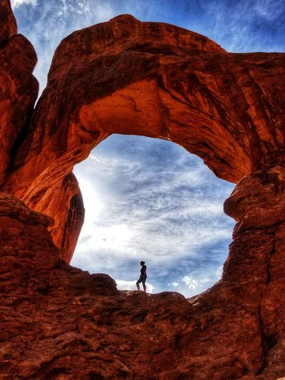 Woman On Rock Formation Against Sky