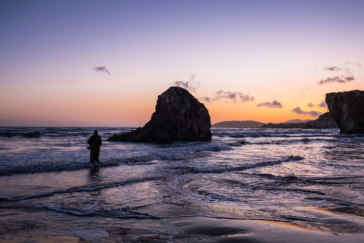 Lonely fisherman trying his luck // Beach Beauty In Nature California Coastline Copy Space Fisherman Horizon Over Water Idyllic Leisure Activity Lifestyles Light And Shadow Nature Rock - Object Rock Formation Romantic Scenics Sea Shore Sun Sunset Tranquil Scene Unrecognizable Person Watching Water Wave
