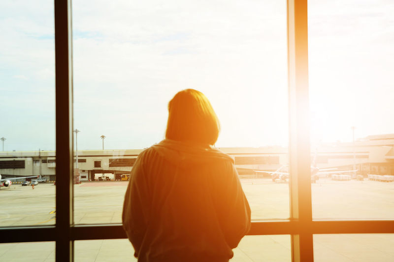 Rear view of woman standing by window at airport terminal