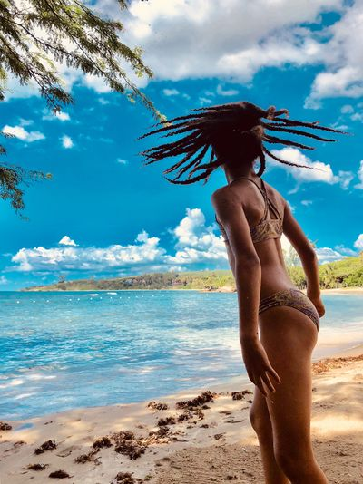 Girl with tousled dreadlocks at beach