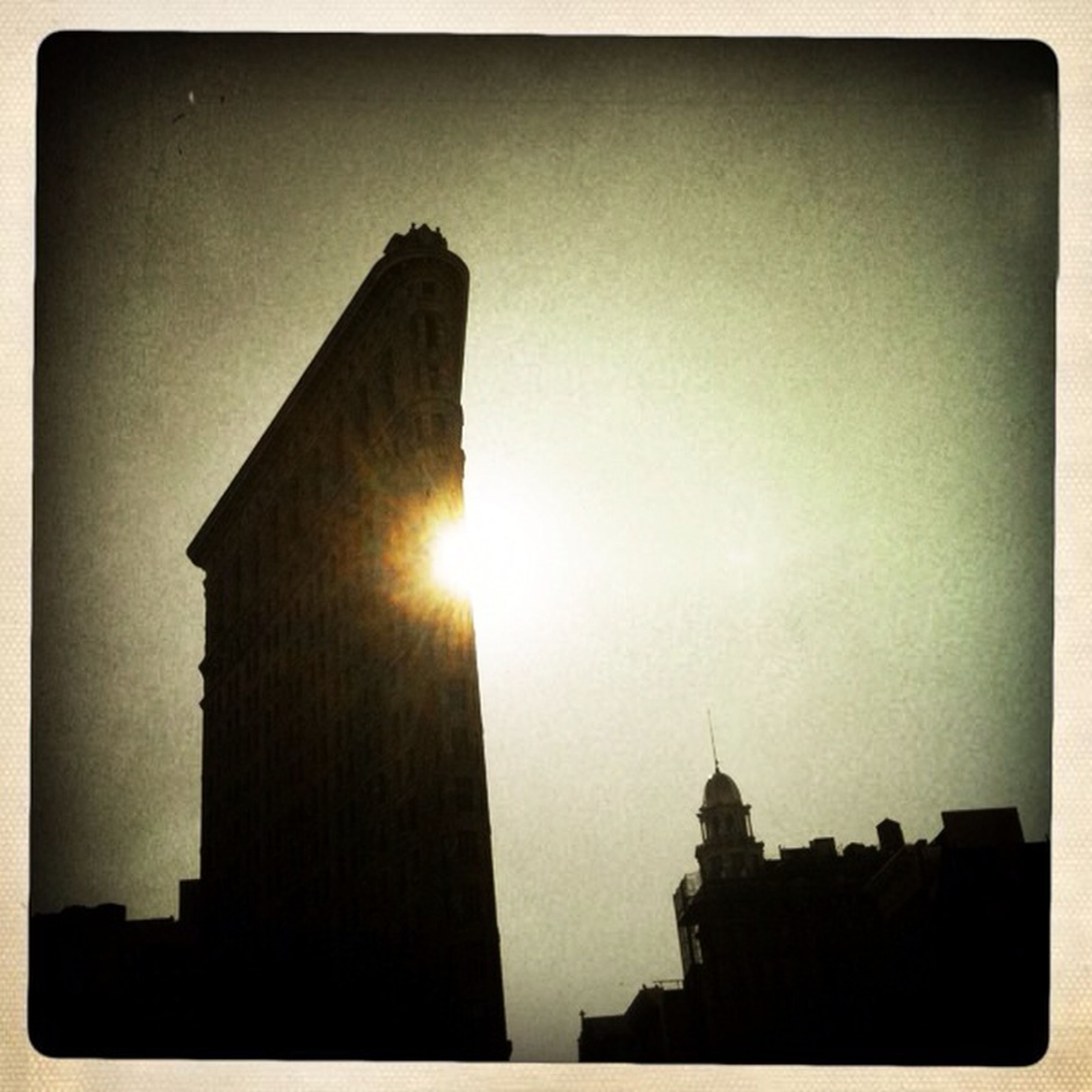architecture, building exterior, built structure, sun, low angle view, silhouette, transfer print, sky, auto post production filter, sunset, sunbeam, sunlight, lens flare, tower, clear sky, outdoors, religion, no people, city
