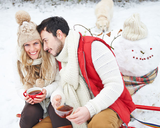 Couple having tea while sitting on snow covered field