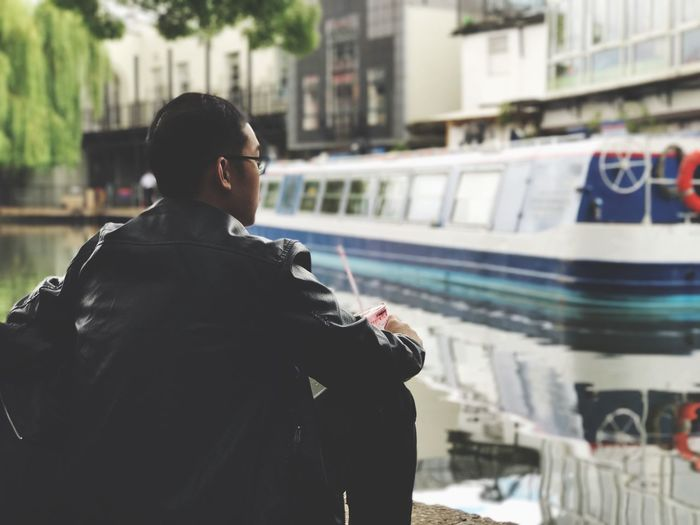 Rear view of young man sitting by canal in city