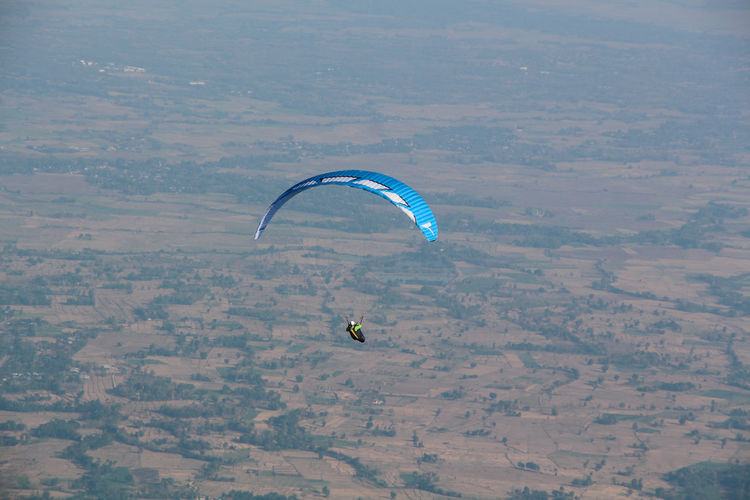 People paragliding over landscape