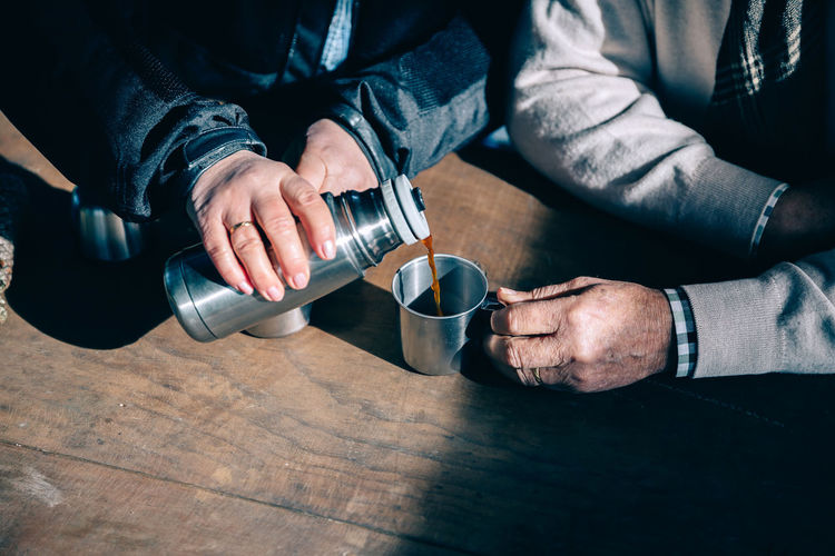 Close up of senior couple hands pouring coffee in a metal cup from thermos over a wooden table Coffee Couple Hands Horizontal Hot Love Man Pouring Tea Thermos Wanderlust Woman Close Up Cup Drink Female Holding Lifestyles Male Metal Senior Table Togheter Two People Unrecognizable