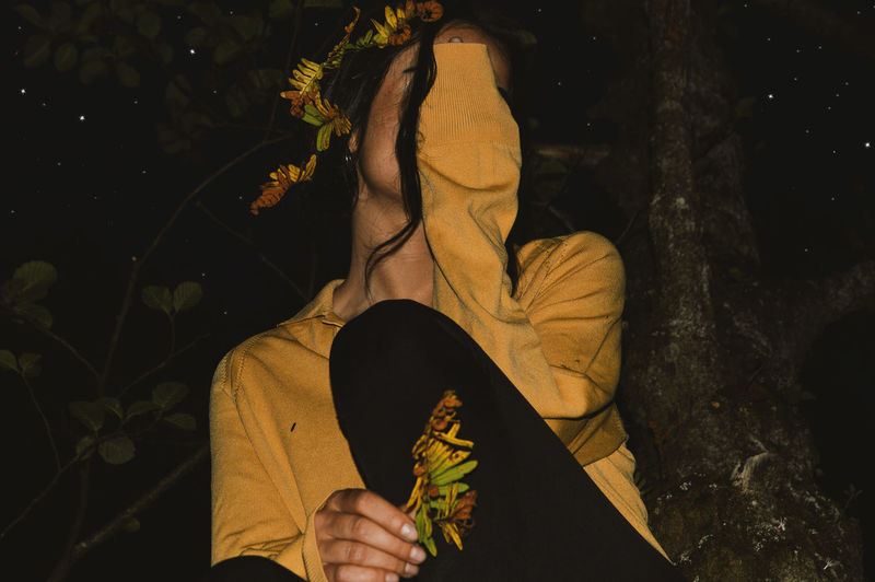 Close-Up Of Woman Sitting Against Tree At Night