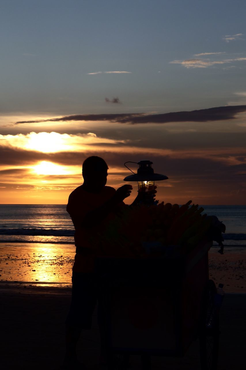 sunset, sea, real people, sky, silhouette, nature, water, beauty in nature, leisure activity, cloud - sky, men, scenics, standing, beach, horizon over water, one person, outdoors, lifestyles, technology, photographing, people