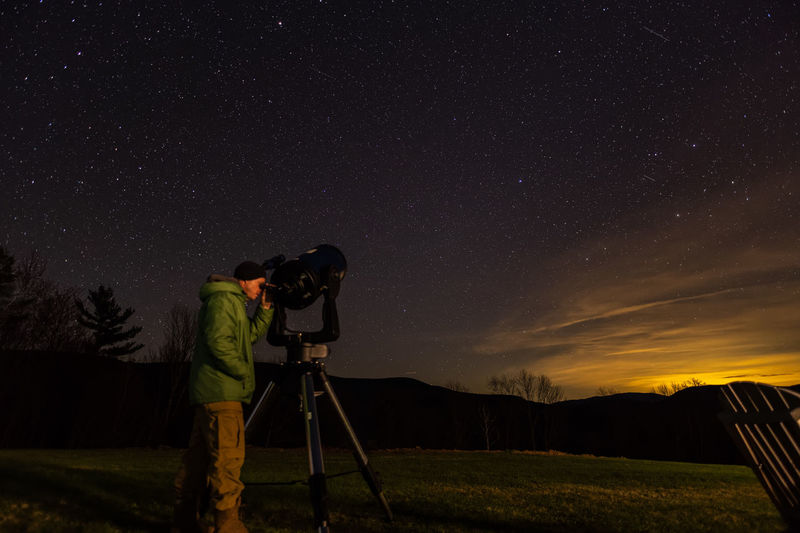 Man photographing against sky at night